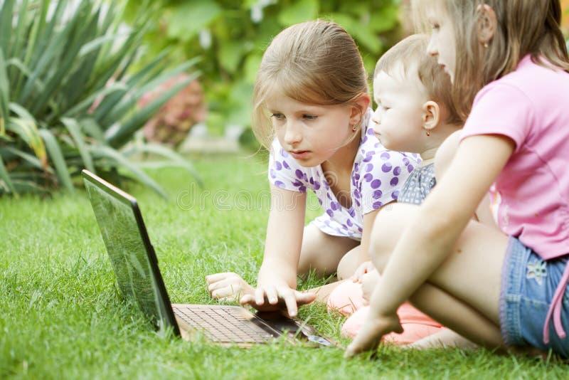 Crianças que usam o portátil no prado fotos de stock royalty free