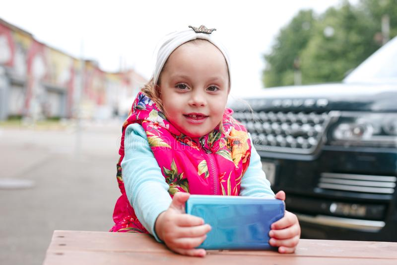 Crianças que usam o telefone esperto Bebê que joga o telefone celular exterior imagens de stock