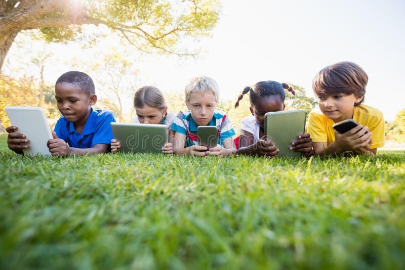 Crianças que usam a tecnologia durante um dia ensolarado foto de stock