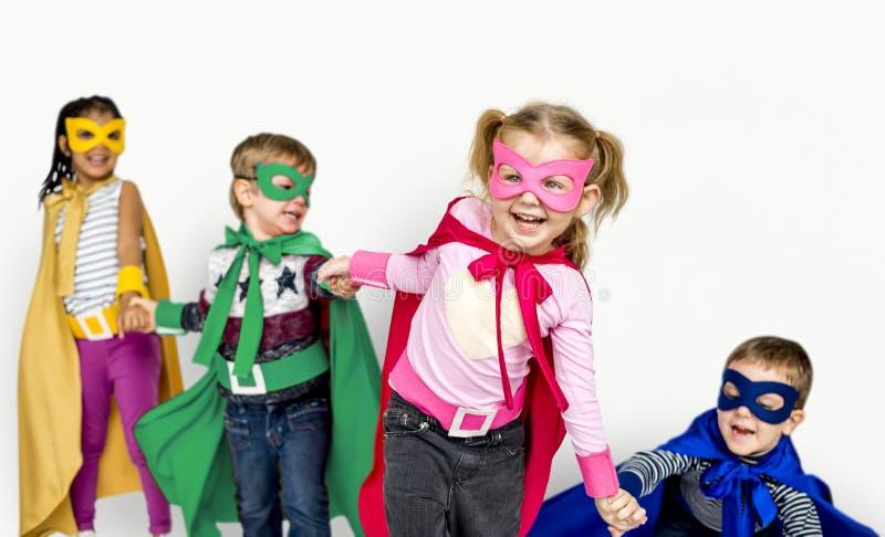 Crianças que vestem as mãos da posse do super-herói fotos de stock