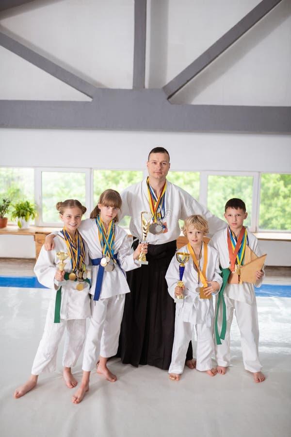 Crianças que vestem as medalhas que estão perto de seu instrutor favorito fotos de stock royalty free