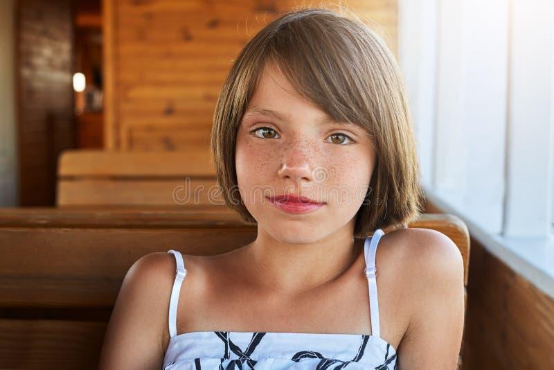 Crianças, resto, conceito do abrandamento Agradável-olhando a menina freckled com cabelo escuro curto, vestido vestindo do verão  imagem de stock royalty free