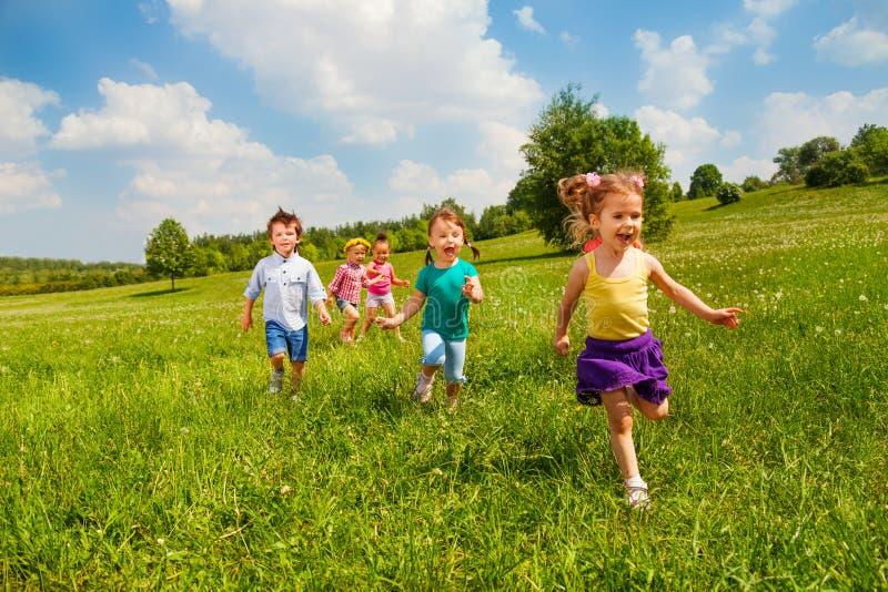 Crianças running no campo verde durante o verão fotos de stock royalty free