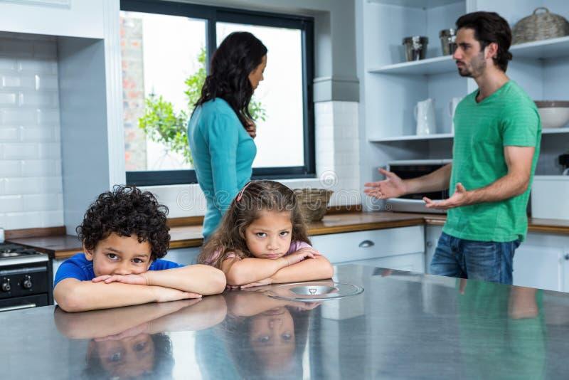 Crianças tristes que escutam o argumento dos pais imagens de stock