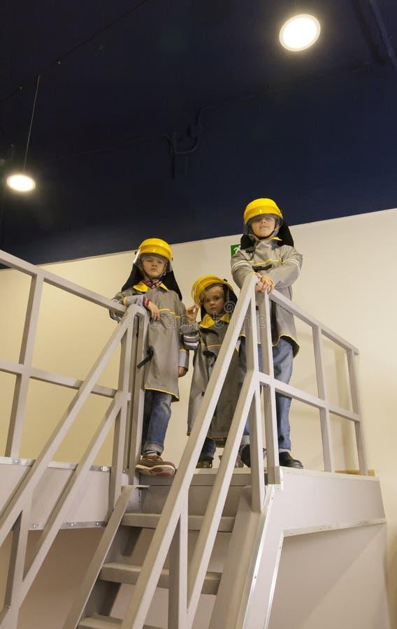 Crianças vestidas nos trajes dos sapadores-bombeiros imagem de stock royalty free