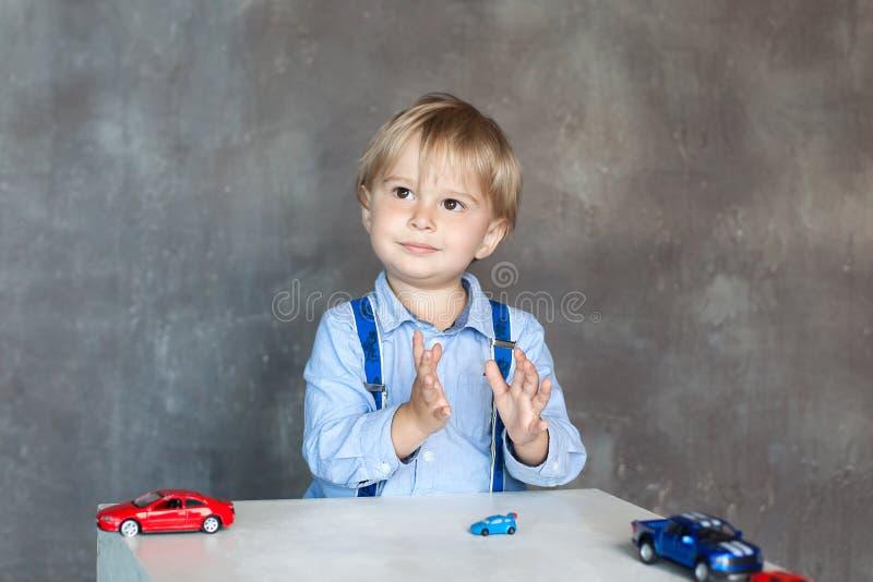 A crian?a aplaude suas m?os Retrato de um rapaz pequeno bonito que joga com carros Menino pré-escolar que joga com os carros do b fotografia de stock royalty free