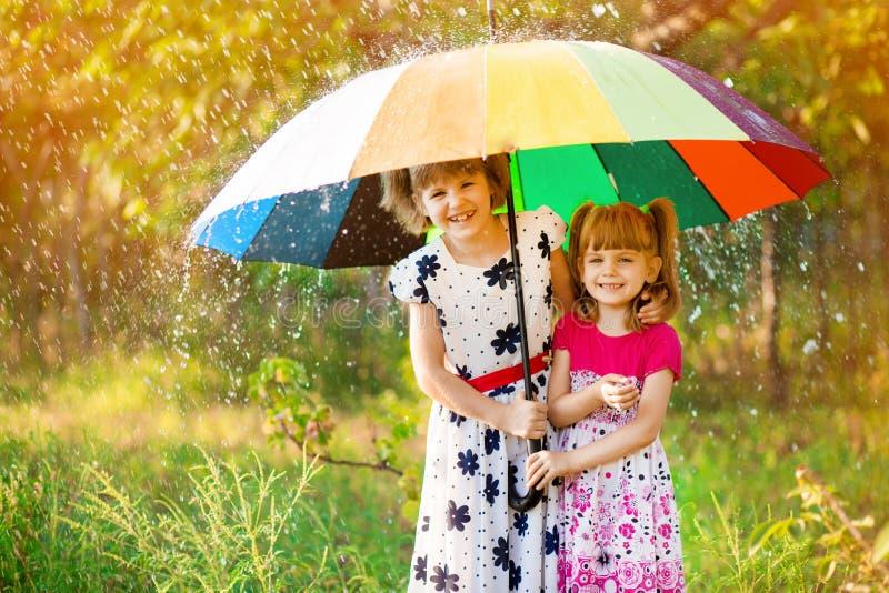 Crian?as com o guarda-chuva colorido que joga na chuva do chuveiro do outono As meninas jogam no parque pelo tempo chuvoso foto de stock royalty free