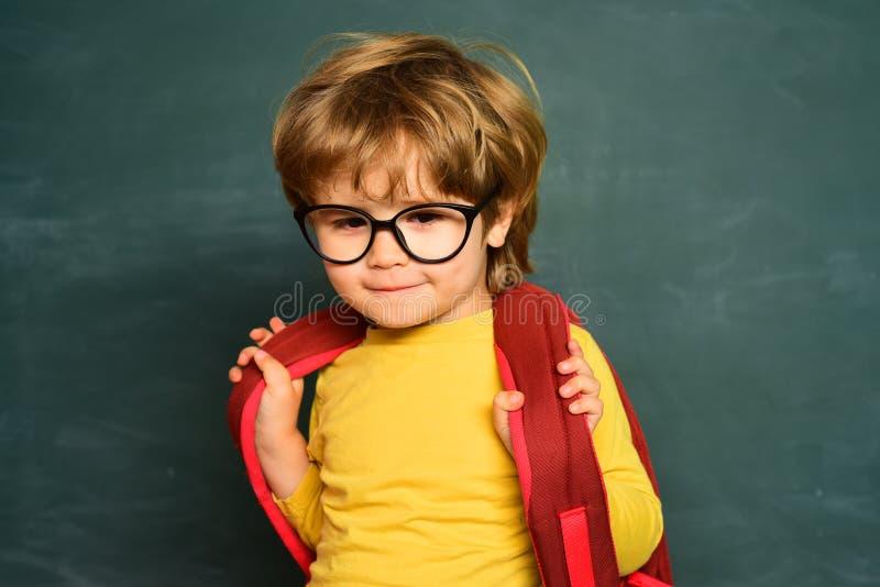 Crian?as da escola A crian?a est? aprendendo na classe no fundo do quadro-negro Aprendendo o conceito Menino pr?-escolar pequeno  fotos de stock
