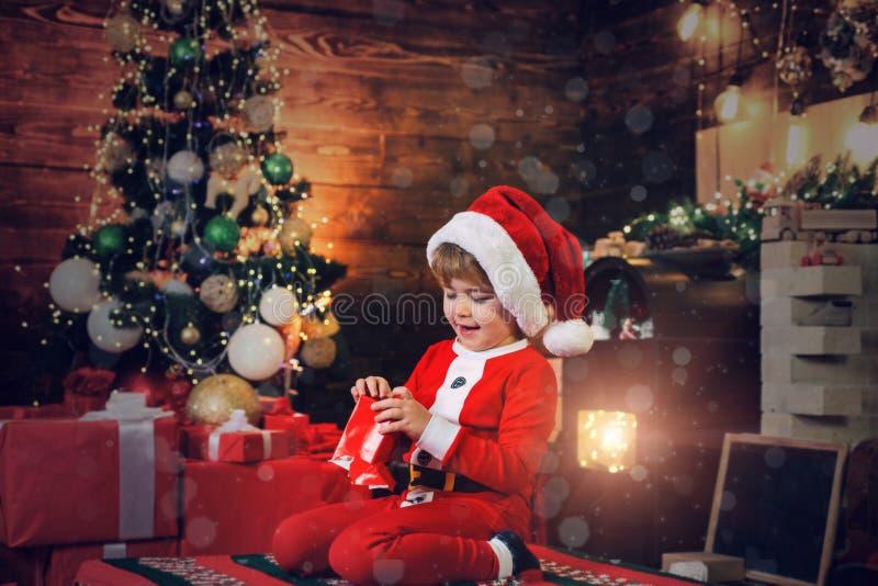 Crian?as do Natal A crian?a feliz est? vestindo a roupa de Santa, jogando com caixa de presente do Natal Fundo da chamin? fotografia de stock