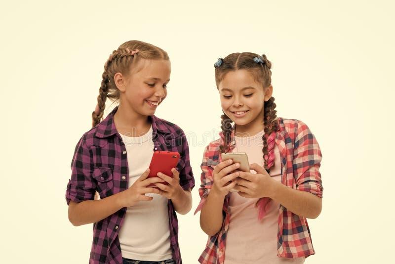 Crian?as pequenas bonitos das meninas que sorriem para telefonar ? tela Gostam de redes sociais surfar de Internet Problema de no fotos de stock