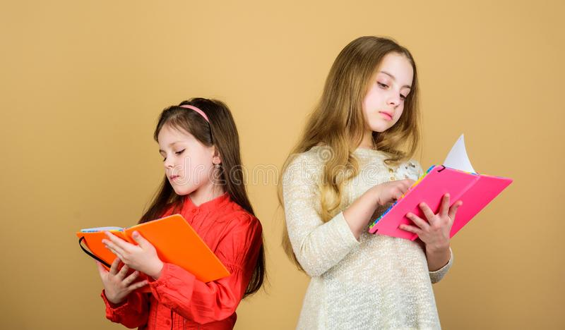 crian?as pequenas felizes prontas para a li??o da escola Estudantes que l?em um livro Projeto da escola Amizade e irmandade imagem de stock