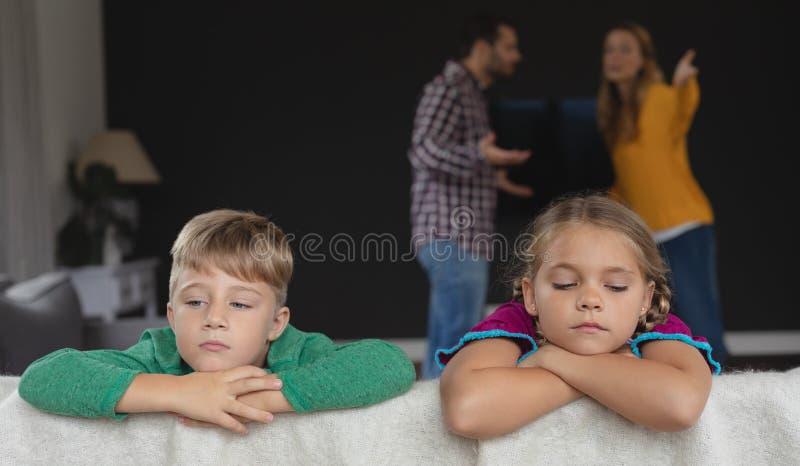 Crian?as tristes que inclinam-se no sof? quando pais que discutem no fundo imagem de stock