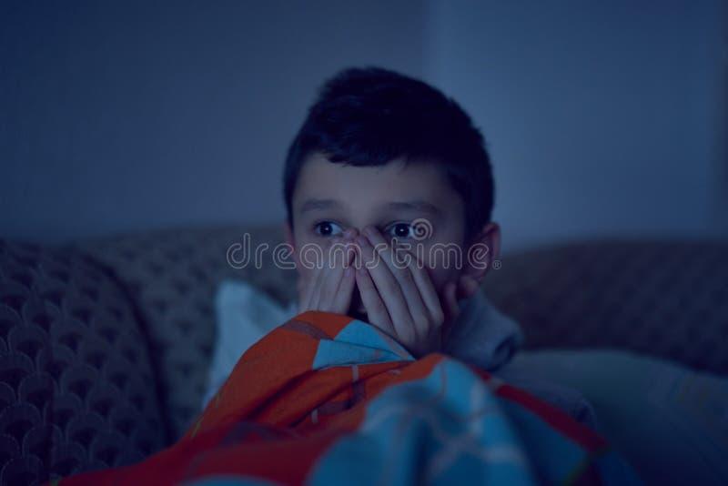 Crian?a assustado que olha o filme assustador na tev?, sentando-se no sof? na noite fotos de stock royalty free
