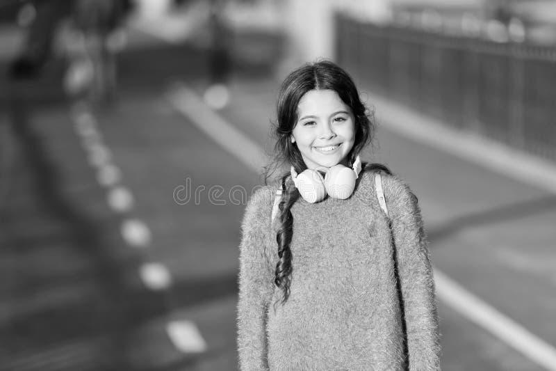 Crian?a bonito da menina ativa da lista do jogo da m?sica do estilo de vida com fones de ouvido Raz?es voc? deve usar fones de ou fotografia de stock royalty free