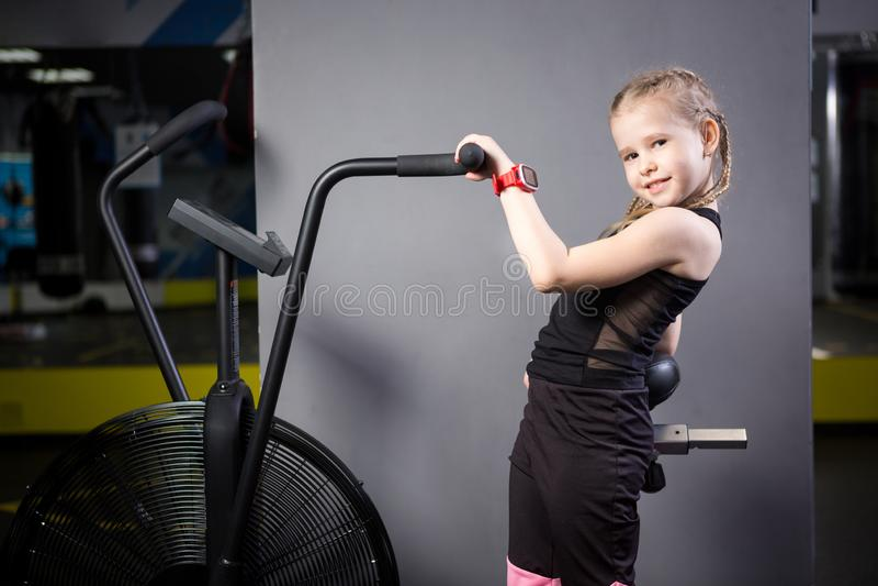 Crian?a caucasiano atrativa pequena que usa a bicicleta de exerc?cio no gym Aptid?o Um atleta pequeno que usa uma bicicleta do ar imagem de stock royalty free