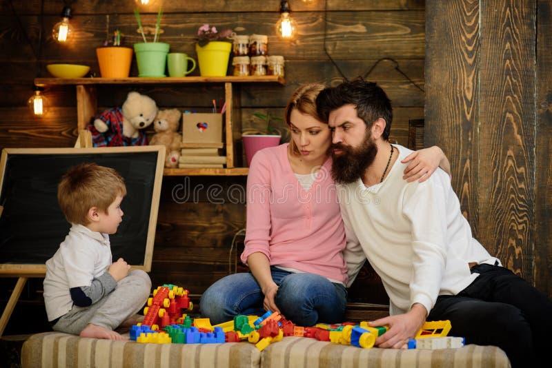 A crian?a com pais joga com blocos pl?sticos, constru??o da constru??o Pai, mãe e jogo bonito do filho com construtor fotografia de stock