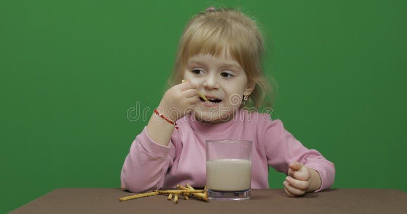 A crian?a come bolinhos Uma menina est? comendo as cookies que sentam-se na tabela fotografia de stock