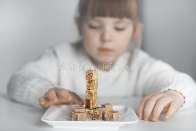 Crian?a, cubos do a??car O problema do consumo excessivo de açúcar por crianças foto de stock royalty free