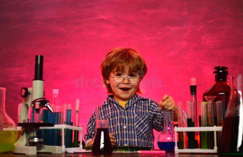 Crian?a da escola prim?ria Microsc?pio do laborat?rio e tubos de testes De primeiro grau De volta à escola e ao tempo feliz a cri imagens de stock