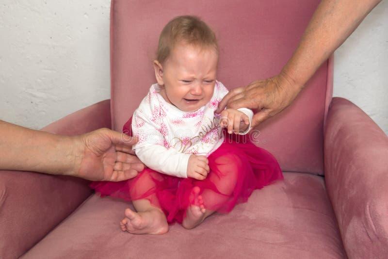 Crian?a de grito Crise hist?rica da crian?a Emo??es negativas da crian?a, crian?a Beb? que senta-se na cadeira no vestido cor-de- imagens de stock