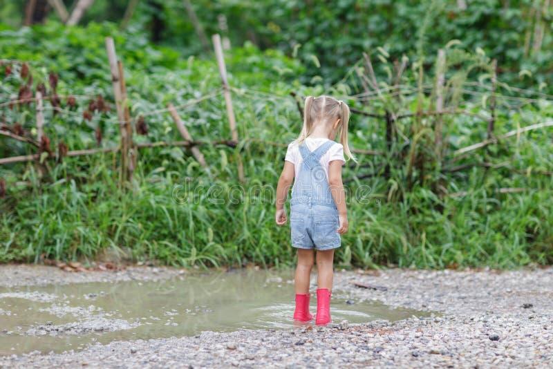Crian?a em botas de borracha cor-de-rosa na chuva que salta nas po?as Crian?a que joga no parque do ver?o Divertimento exterior p imagem de stock royalty free