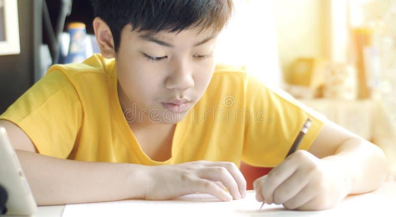 A crian?a escreve trabalhos de casa Crian?as a fazer trabalhos da casa na tabela na sala de visitas imagens de stock