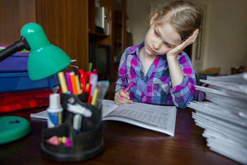 A crian?a faz seus trabalhos de casa, escrevendo e aprendendo Atenção cansado e dispersada da menina foto de stock royalty free