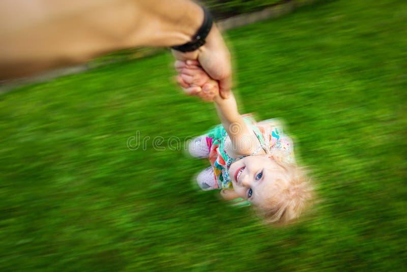 A crian?a feliz est? jogando com pai em casa pai que guarda sua filha à mão e que gerencie ao redor fotos de stock royalty free