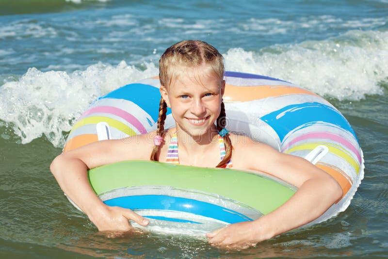 Crian?a feliz que joga na ?gua azul do oceano em um recurso tropical no mar Nadadas alegres da menina no oceano azul com fotografia de stock