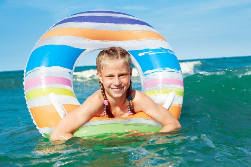 Crian?a feliz que joga na ?gua azul do oceano em um recurso tropical no mar Nadadas alegres da menina no oceano azul com foto de stock royalty free