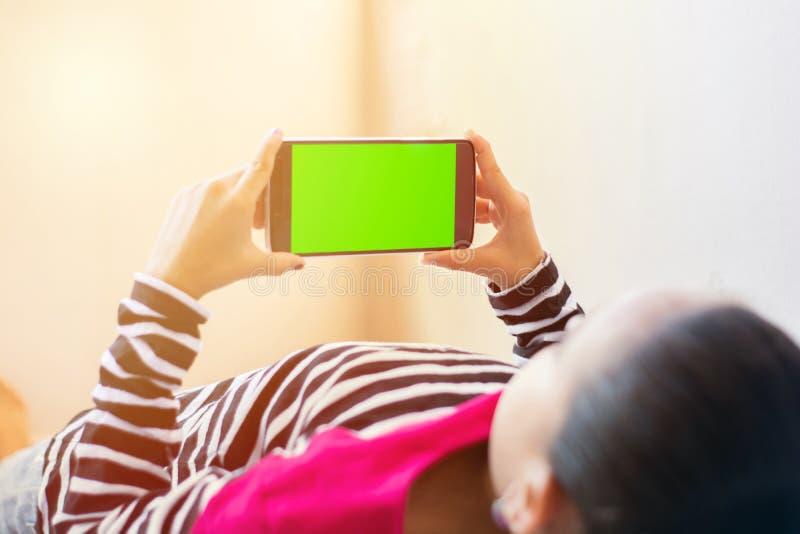 Crian?a indiana pequena com o telefone em suas m?os que dorme na cama, trocista acima com tela verde, foco no telefone fotos de stock