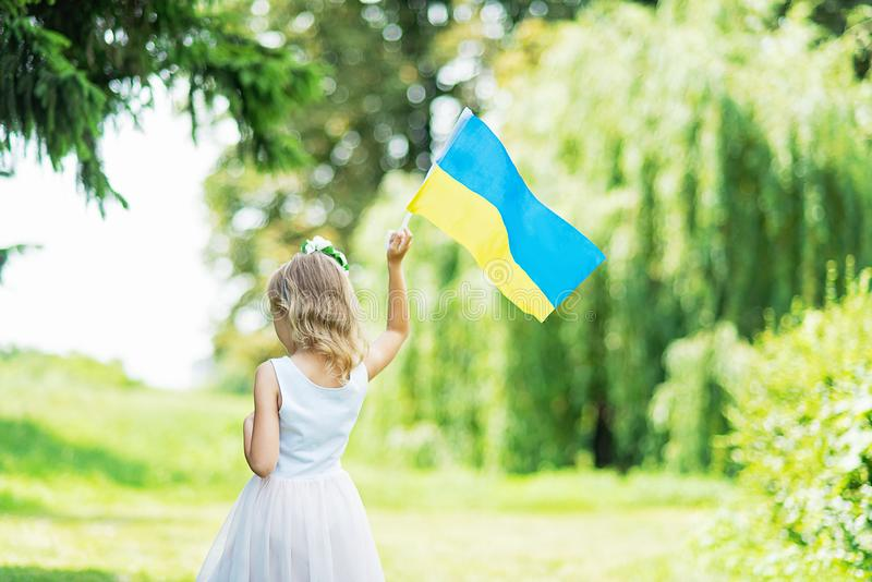 A crian?a leva a vibra??o bandeira azul e amarela de Ucr?nia no campo Dia da Independ?ncia do ` s de Ucr?nia Dia de bandeira Dia  imagem de stock royalty free