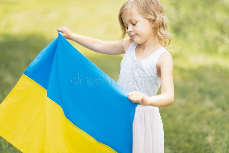 A crian?a leva a vibra??o bandeira azul e amarela de Ucr?nia no campo Dia da Independ?ncia do ` s de Ucr?nia Dia de bandeira Dia  foto de stock