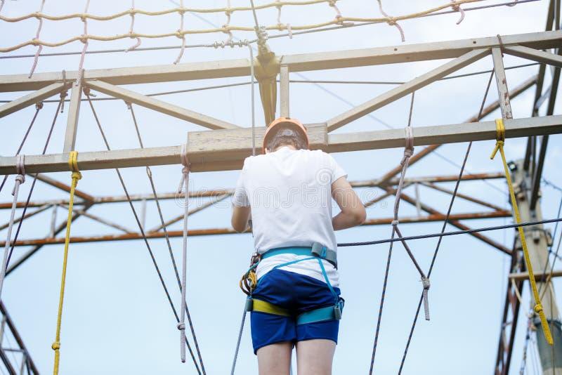 Crian?a no parque da aventura da floresta A criança no capacete alaranjado e na camisa branca de t escala na fuga alta da corda H imagens de stock