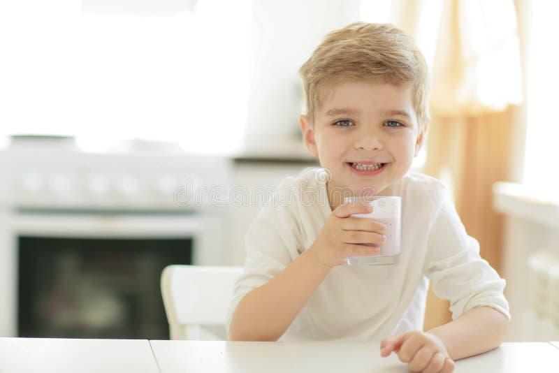 Crian?a ou menino feliz louro que comem na tabela Inf?ncia e felicidade, independ?ncia Caf? da manh?, manh?, fam?lia Menino peque fotos de stock