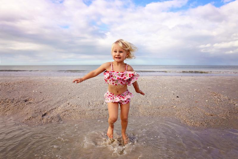 Crian?a pequena bonito que espirra e que joga na ?gua na praia pelo oceano fotografia de stock