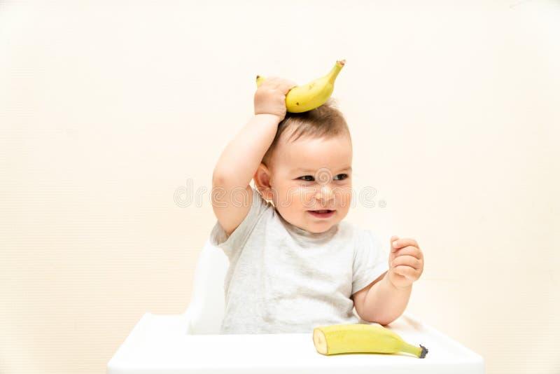 Crian?a pequena engra?ada que come a banana em um beb? do alimento de espa?o da c?pia da cadeira alta fotografia de stock