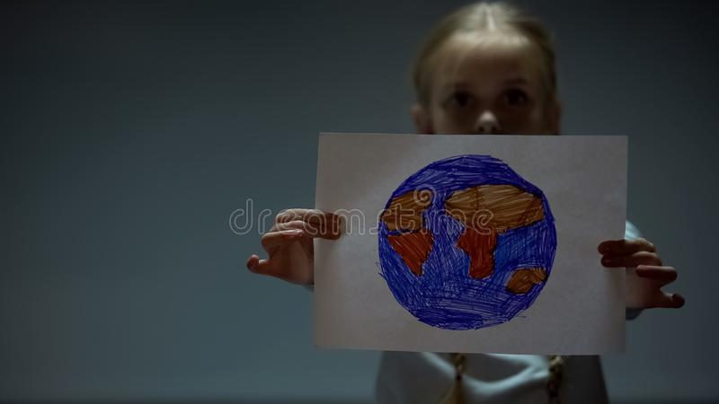A crian?a pequena que mostra a imagem da terra na c?mera, para o conceito da globaliza??o foto de stock