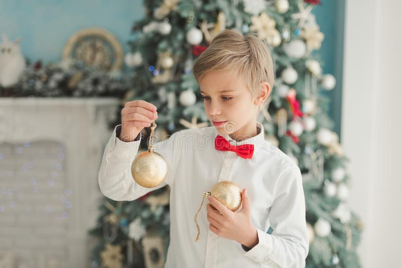 Crian?a que decora a ?rvore de Natal em casa O menino pendura bolas do Natal na árvore Conceito da Noite de Natal fotografia de stock royalty free