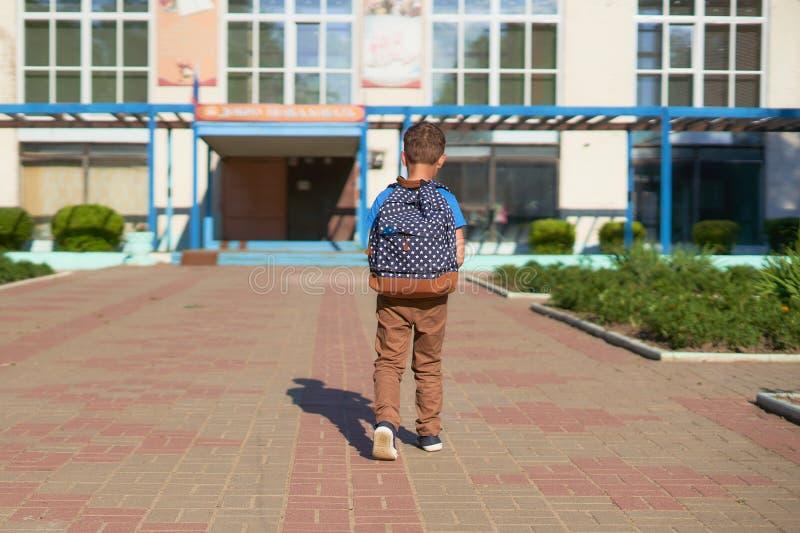 A crian?a vai ? escola a estudante do menino vai educar na manhã criança feliz com uma pasta no seu para trás e em livros de text foto de stock royalty free