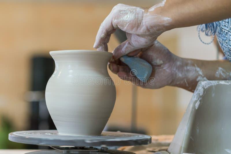 Criando um frasco ou um vaso do close-up branco da argila Vasilha de barro mestra Mãos do homem que fazem o macro do jarro da arg fotos de stock