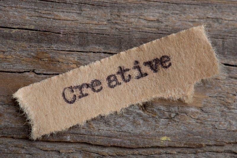 Criativo - palavra em um fim do pedaço de papel acima, conceito criativo da motivação do negócio fotografia de stock