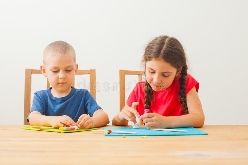 Criativos moldando crianças em casa de mesa imagens de stock