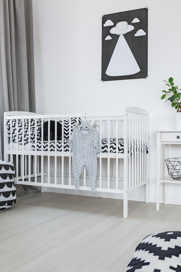 Crib in baby room. White crib in spacious baby room stock photos