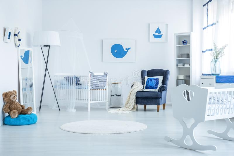 Crib and cradle. Wooden crib and white cradle standing in newborn`s room with posters and armchair royalty free stock image