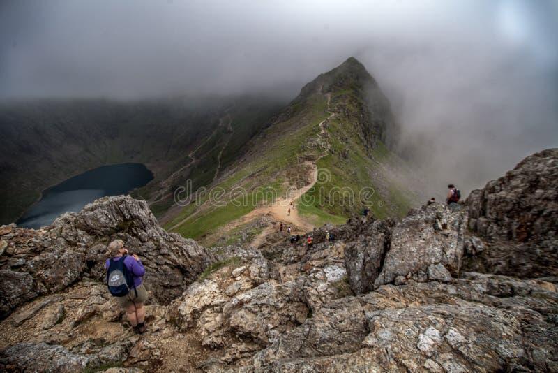 Crib Goch Ridge, Snowdonia, Wales. Hikers on rocky crag of Crib Goch Ridge, Snowdonia, Wales with fog stock images