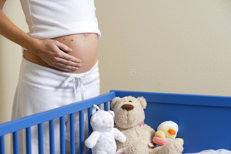 Crib and Toys. A pregnant woman loves her un-born baby near a crib with stuffed animals stock photos