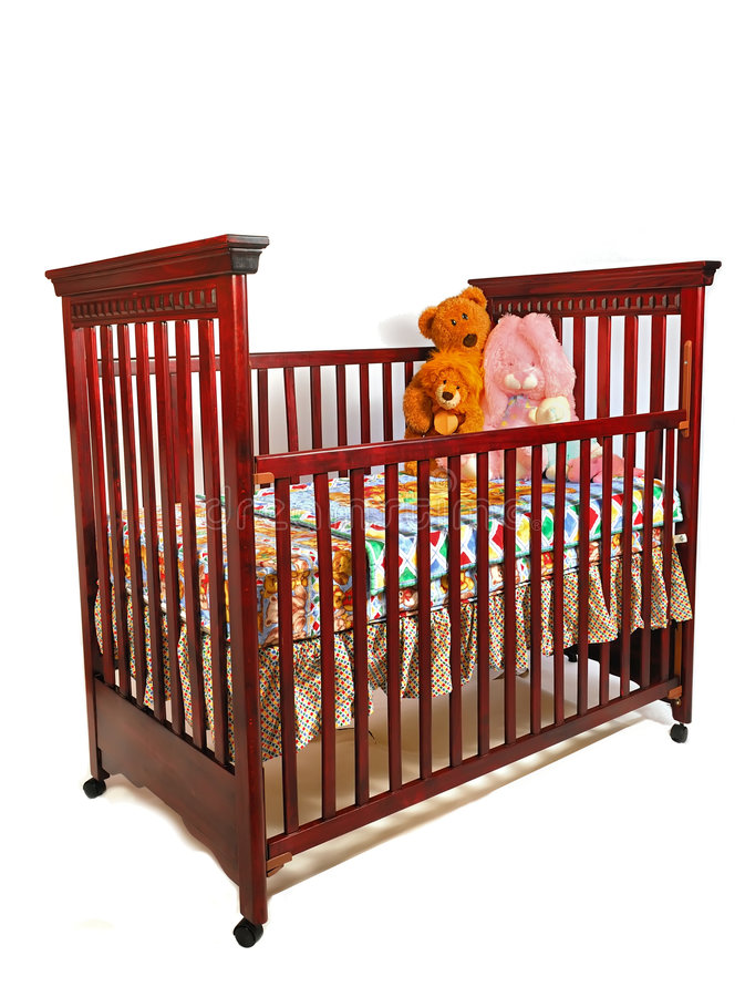 Crib Waiting For Baby. A dark cherry crib is dressed for baby, placed against white royalty free stock image