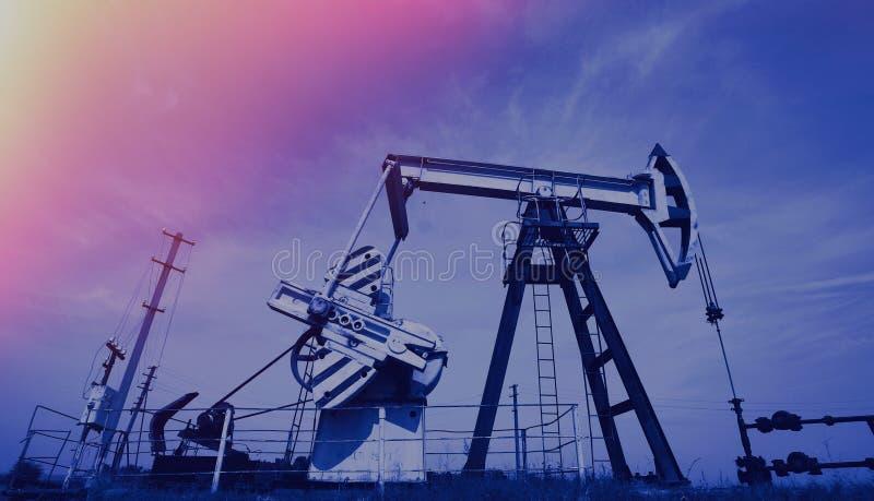 Cric de pompe d'extraction du pétrole et tête de puits d'huile modifiée la tonalité photographie stock