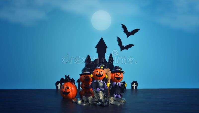 Cric-o-lanterne de potirons de Halloween avec des affaires croissantes de pile de pièce de monnaie d'argent sur le fond bleu-fonc photo stock